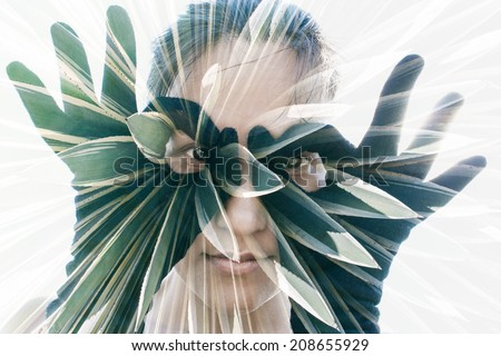 Double exposure portrait of attractive woman in black gloves forming glasses combined with photograph of cactus - stock photo