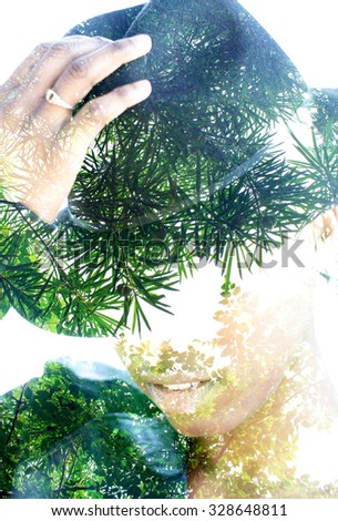 Double exposure portrait of woman with hat combined with photograph of tree - stock photo