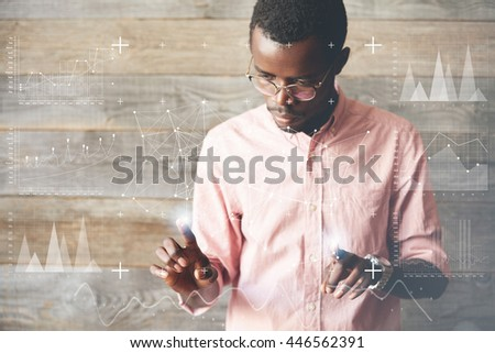 Double exposure. Young dark-skinned student, presenting his futuristic graduation project, pressing on glowing elements on a futuristic touchscreen interactive board, against wooden wall background - stock photo