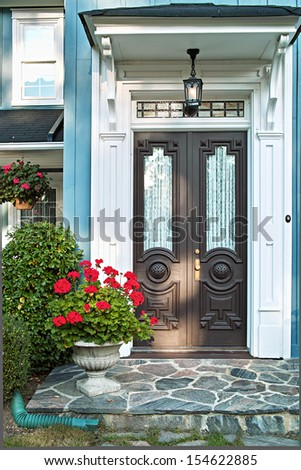 Double front door of luxurious landscaped home - stock photo