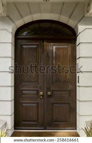 Double Front Doors Surrounded by Stone Arch with Overhead Window - stock photo