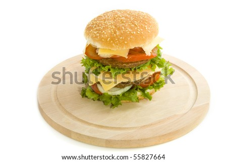 Double hamburger on a wooden plate isolated over white