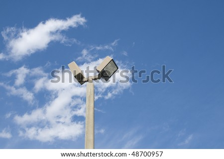 Double headed street light on a concrete pole with partly cloudy blue sky