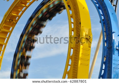 Double Loop on a Roller Coaster with train just passing. - stock photo