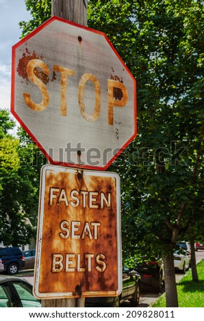 Double messages on this pole...stop, and, fasten your seat belt...look like they have been here for a lot of years - stock photo
