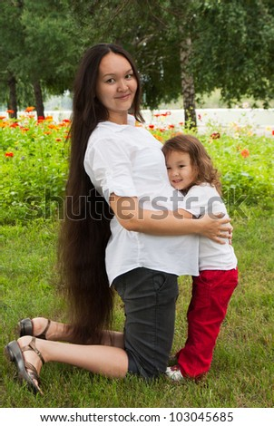 Double motherhood - pregnancy woman and her little daughter in a summer garden