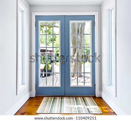 Double patio french doors with windows exiting to sunny backyard - stock photo