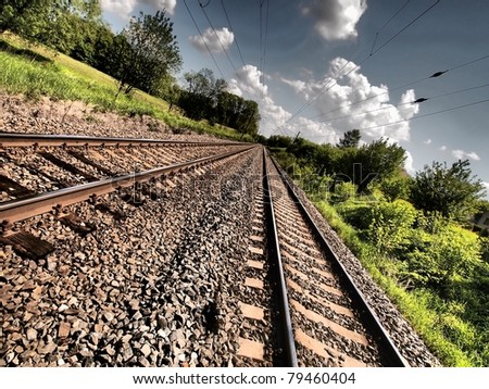 Double railroad track with HDR effect leading into the distance - stock photo