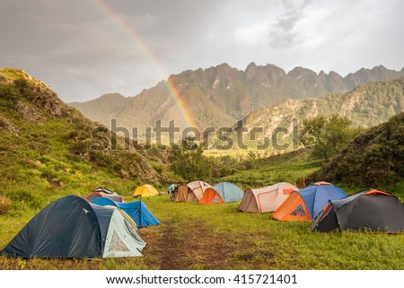 Double rainbow at campsite in mountains - stock photo