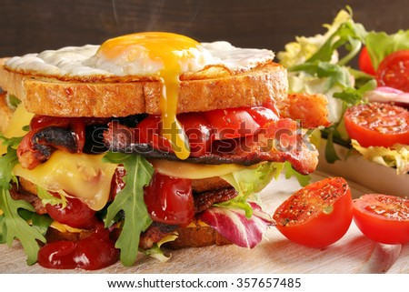 Double sandwich with bacon cheese and egg on wooden background