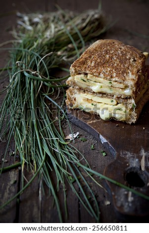 double sandwich with omelette and chives on rustic wooden table with bunch of freshly harvested chives - stock photo