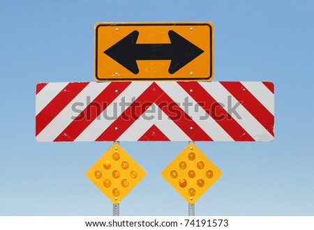 double sided arrow and reflective warning signs at a T junction on a road - stock photo