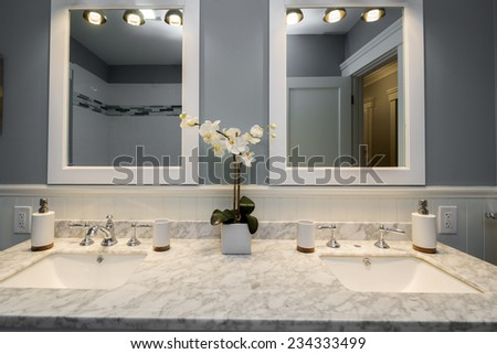 Double sink in luxurious bathroom with white honed Marble and tile in the Shower - stock photo