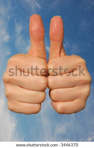 Double Thumbs Up against blue sky - stock photo