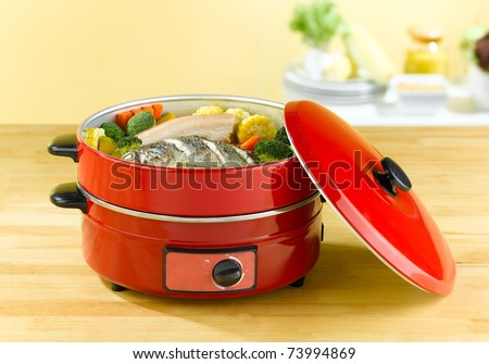 Double tray steaming electric pot, 2 purpose for steam cooking and frying food - stock photo
