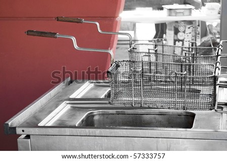 Double used restaurant fryer in open space by a red wall - stock photo