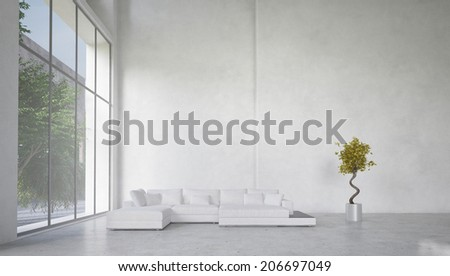 Double volume spacious living room interior with huge panoramic windows overlooking a garden and a corner unit white lounge suite against a bare white wall - stock photo