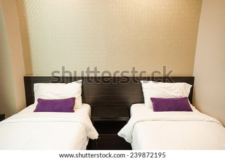 Double white bed and purple pillow - stock photo