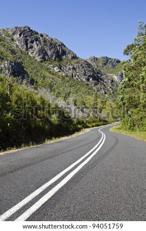 Double white lines on highway through mountains near Tullah, West coast, Tasmania, Australia - stock photo