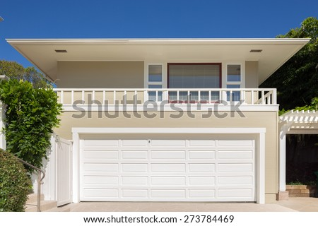 Double white painted garage doors exterior in flat roof house.  - stock photo