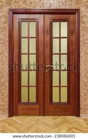 double wooden doors with cork wallpaper and flooring - stock photo