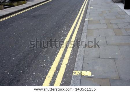 Double yellow line on London street - stock photo