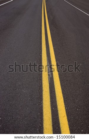Double yellow road lane stripes on new highway showing no wear.