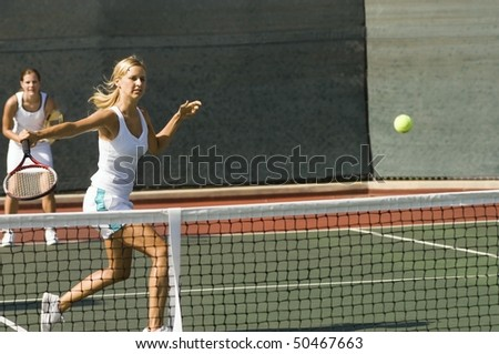 Doubles tennis Player Hitting tennis ball with Backhand - stock photo