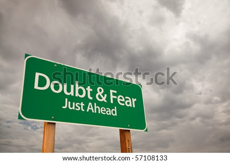 Doubt and Fear Just Ahead Green Road Sign with Dramatic Storm Clouds and Sky. - stock photo