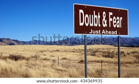 Doubt and Fear road sign with blue sky and wilderness - stock photo
