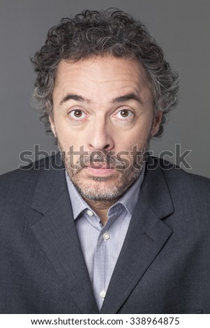 doubt and surprise concept - portrait of amazed mature businessman surprised by corporate strategy,grey background