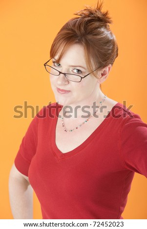 Doubtful Caucasian woman on an orange background - stock photo