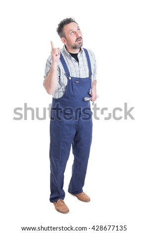 Doubtful young mechanic showing something by pointing finger up with fixing tool in his hand isolated on white background - stock photo