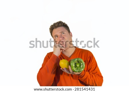 Doubting guy holding fruits and vegetables, specifically a pepper and lemon