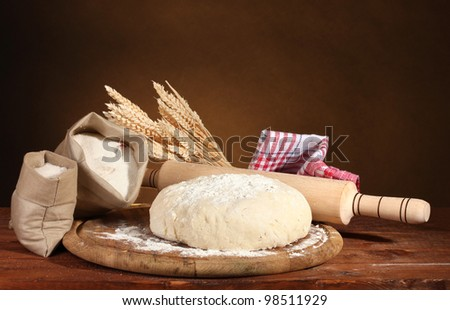 Dough and bags with flour on wooden table on brown background - stock photo