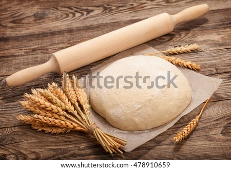 dough and ears of wheat on the old board.