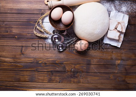Dough and ingredients for it - eggs, flour, yeast on dark wooden background. Selective focus. Place for text. - stock photo