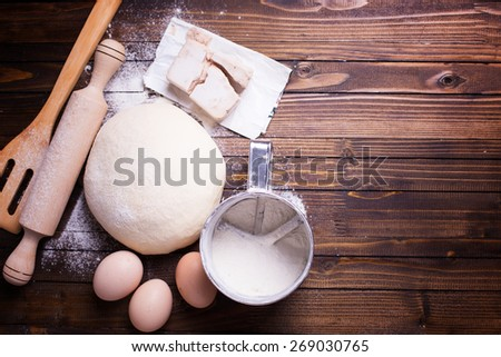Dough and ingredients for it - eggs, flour, yeast on dark wooden background. Selective focus. Place for text. Toned image. - stock photo