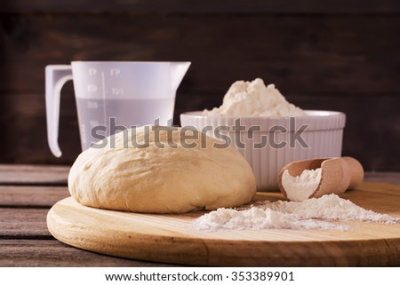 Dough and ingredients for it -  flour, water on dark wooden background. Selective focus.