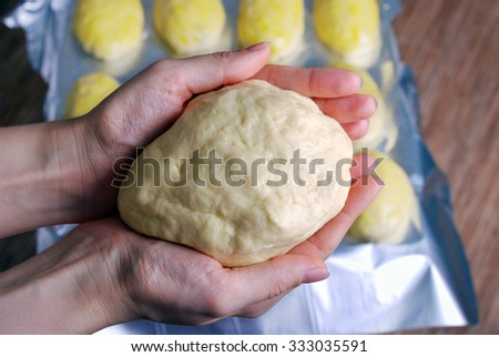 dough for buns in their hands