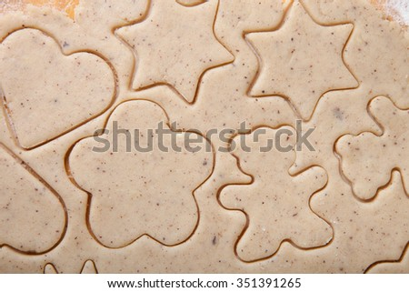 Dough for gingerbread cookie and cookie cutted in different shapes like background. - stock photo