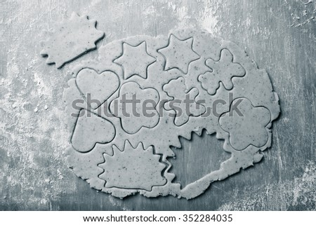 Dough for gingerbread cookie and cookie cutted in different shapes on light wooden cutting board like background. Toned.
