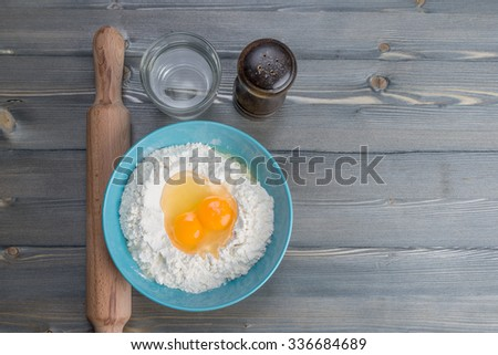 dough for homemade noodles - ingredients (flour, eggs, salt and water) - stock photo