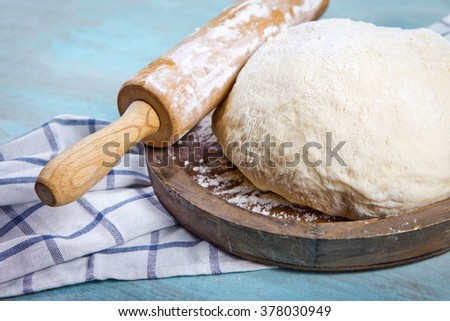 Dough for pizza and rolling-pin on wooden table