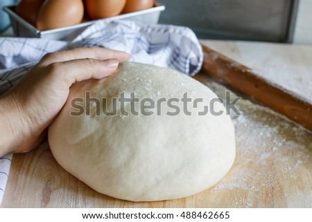 Dough for pizza or bread and rolling-pin on wooden table