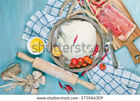 Dough for pizza with ingridients: cherry tomatoes, chili pepper and prosciutto on blue wooden table - stock photo