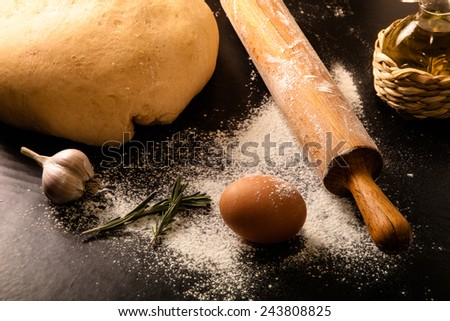 dough on a black board with flour. olive oil, eggs, rolling pin, garlic  - stock photo