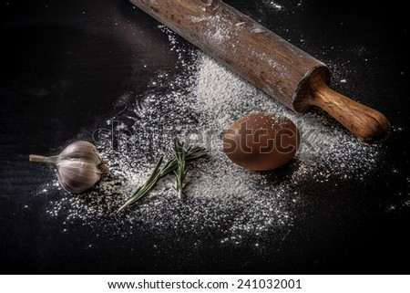 dough on a board with flour.  eggs, rolling pin, garlic  - stock photo