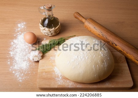 dough on a board with flour. olive oil, eggs, rolling pin, garlic and dill for stuffing - stock photo