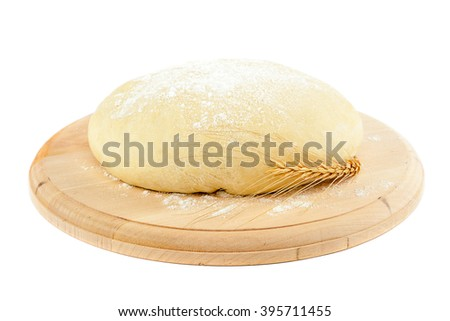 Dough on the wooden board with ears isolated on white background. - stock photo